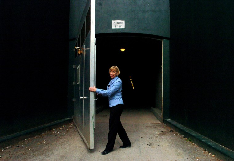 Linda Walls, manager of The Greenbrier's bunker tours, opens one of the giant doors leading to the long-secret fallout shelter built to house Congress after a nuclear attack.