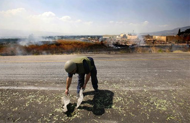 An Israeli policeman inspects the remains of one of nearly 120 rockets that militants in Lebanonfired into northern Israel on Thursday, which forced hotels, hospitals and schools to close.