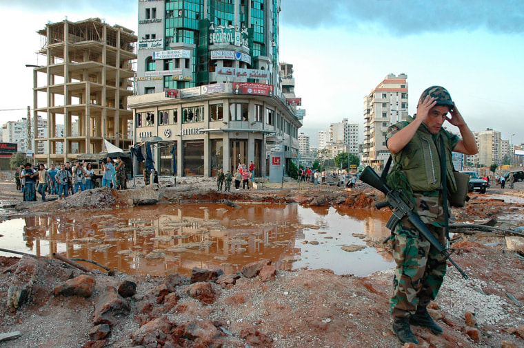 A Lebanese soldier stands next to a crater following Israeli airstrikes at the main Mar Mikhail crossroads in southern Beirut on Friday.