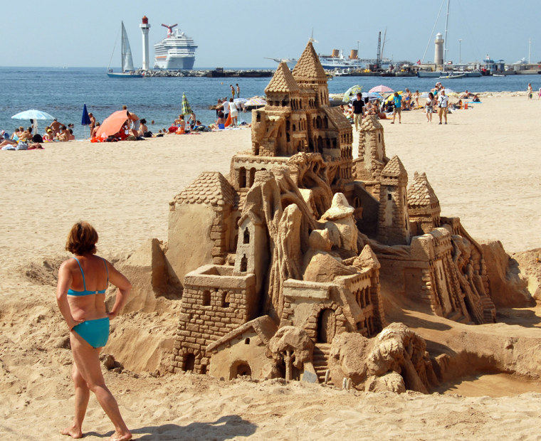 A woman looks at a sand sculpture of a medieval castle Tuesday, July 4, 2006, on a beach in Cannes, France.