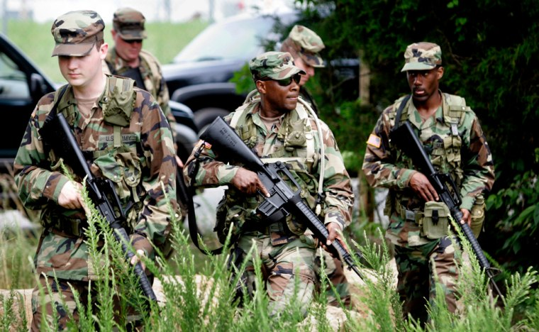 Members of the Virginia National Guard walk a patrol during a training exercise for guard volunteers who are being deployed to the Arizona border with Mexico Tuesday.