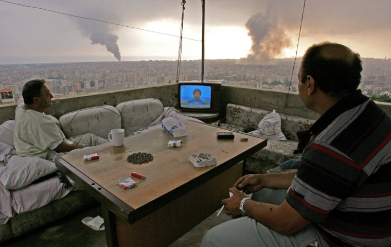 Lebanese citizens watch Hezbollah leader Sheik Hassan Nasrallah speak on television as black smoke rises from new Israeli attacks on the Hezbollah stronghold in the southern suburbs of Beirut, Lebanon, during his speech Sunday.