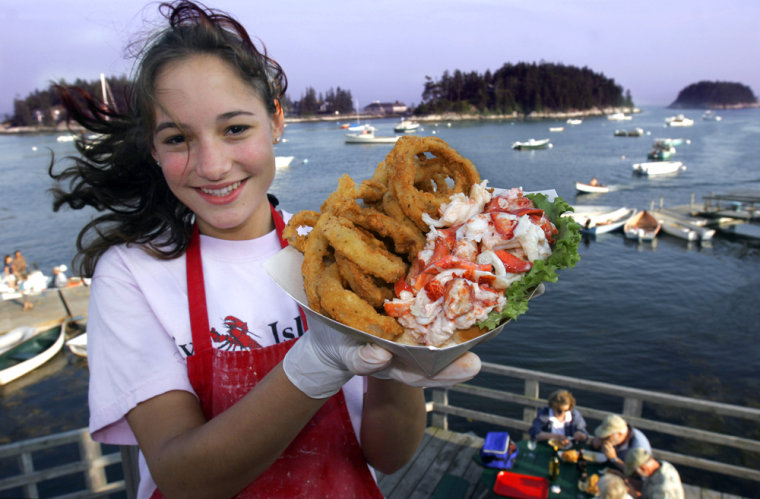 Lesley Spencer of Malvern, Pa., holds up a lobster roll and onion rings at Five Island Seafood in Five Islands, Maine, July 16, 2006.