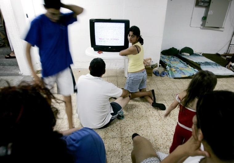 Israeli residents watch television inside a shelter in Nahariya