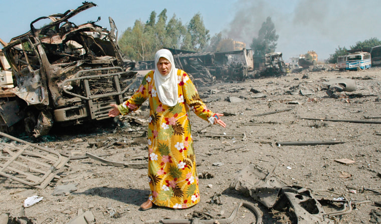 A Lebanese woman reacts after inspecting her truck that was destroyed when it was targeted as part of a convoy by Israeli warplanes, in Hadath, Lebanon, on Wednesday.