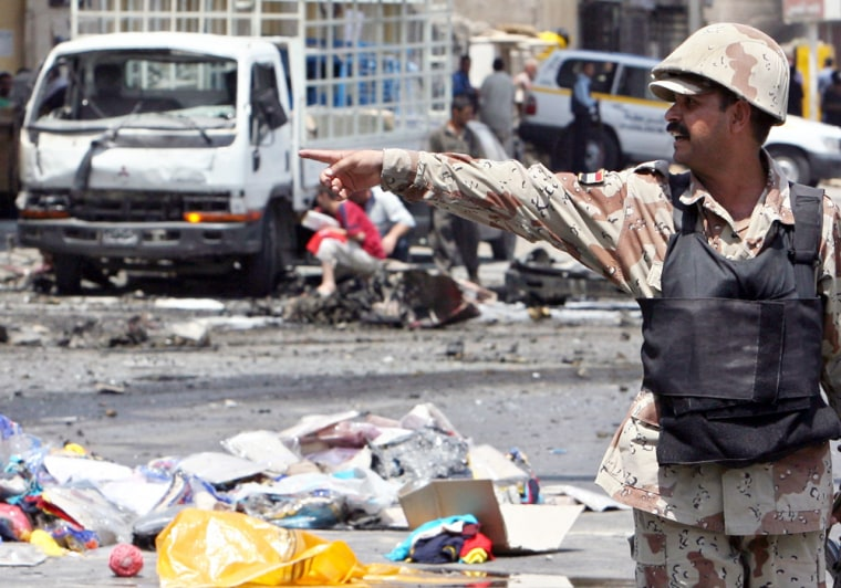 An Iraqi soldier gestures as he secures the site of a car bomb attack in which one man was killed and 15 wounded in central Baghdad