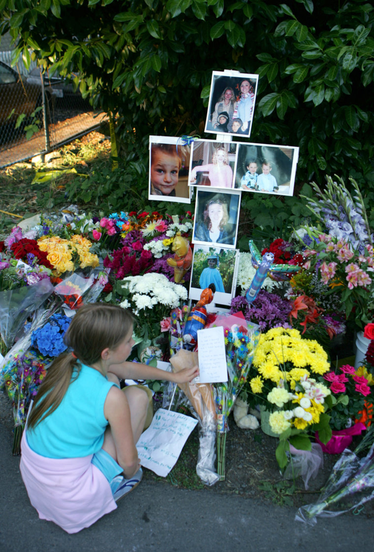 Alina Suyurovsits atthe makeshift memorial for four people killed in a house fire in Kirkland, Wash., on Wednesday. All four people found dead in a home fire Monday were stabbed in the neck before the blaze was set, police say.