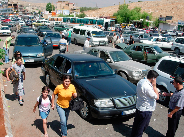 Travelers block the road, at the Masnaa border, between Lebanon and Syria, on the outskirts of the Bekaa Valley, east of Beirut on Monday.