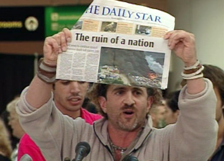 David Merhige, one evacuee from Lebanon, holds up a newspaper to make a point aboutdestruction in the nation as he arrives in Baltimore Thursday.
