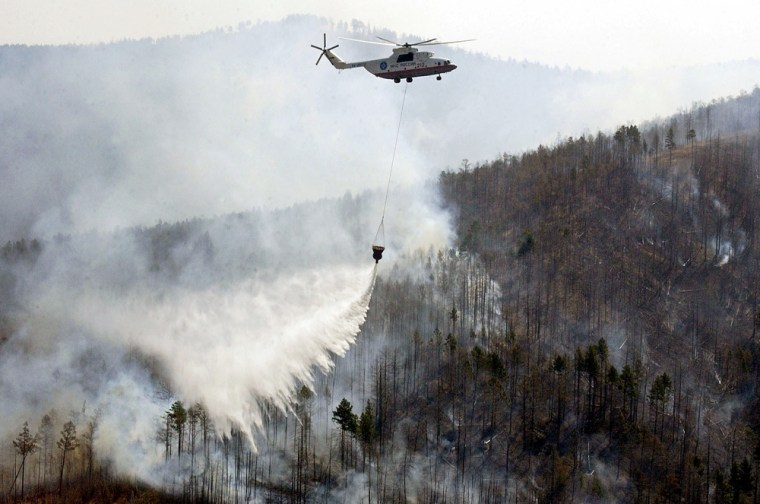 A Russian helicopter dumps water on a 2003 forest fire near the Siberian city of Chita. Researchers find growing evidence tying an upsurge in wildfires to climate change, an impact long predicted by global-warming forecasters.