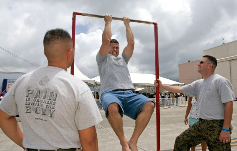 Matt Elam, center, competes in a pull-up contest while Marine recruiters Sgt. Marco Hartanto, left, and Gysgt. Brian Lancioni look on at Marine Corps Base Hawaii onJuly 4 in Kaneohe, Hawaii.
