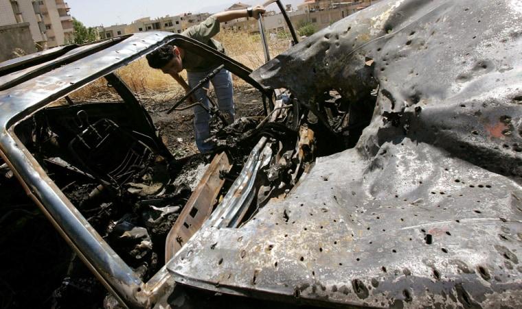 A Lebanese looks at the damage to a car hit by an Israeli air strike in al-Bekaa