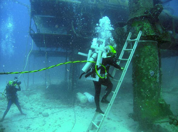 A NEEMO 10 crewmember climbs a ladder during a session of extravehicular activity for the NASA Extreme Environment Mission Operations project. The crewmember is wearing a reconfigurable center of gravity backpack to simulate moonwalking.