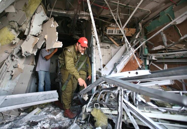 An Israeli policeman surveys a damaged floor at a local clinic in Nahariya