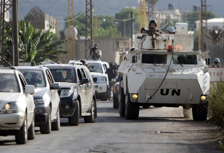 United Nations peacekeepers on an armoured personnel carrier lead a convoy of cars outside the U.N headquarters on the outskirts of the southern border town of Naqoura, Lebanon, on Friday.
