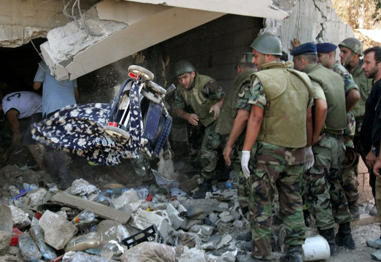 A Lebanese soldier throws a baby stroller Sunday as he and others search for bodies under the rubble of a home hit in an Israeli missile strike in the village of Qana, east of the port city of Tyre.
