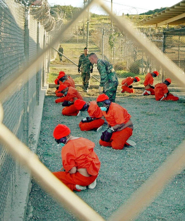 Suspected Taliban and al-Qaida detainees sit in a holding area at Camp X-Ray at Guantanamo Bay, Cuba, during in-processing to the temporary detention facility in this January 2002, photo.
