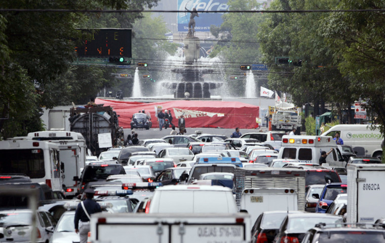 Buses and cars move slowly along the streets Monday in Mexico City. Supporters of the country's leftist presidential candidate paralyzed the city's financial district and refused to leave.