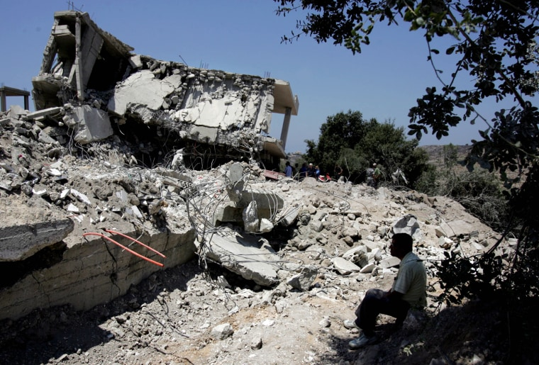 The remains of the house that was hit in an Israeli missile strike are seen in the village of Qana, southern Lebanon, on Monday. At least 56 residents of the village were killed when Israeli warplanes attacked the village early Sunday.