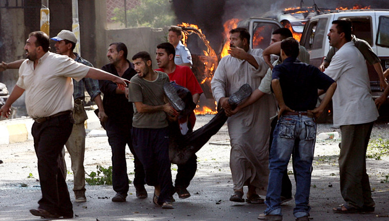 Iraqis wounded in a massive car bomb near a bank in Baghdad are carried awayTuesday morning.
