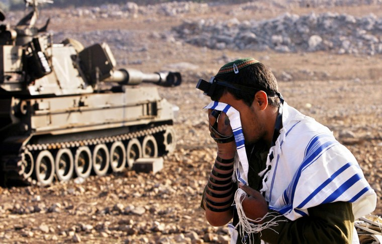 Israeli soldier prays next to mobile artillery unit positioned near northern Israeli town of Fasuta