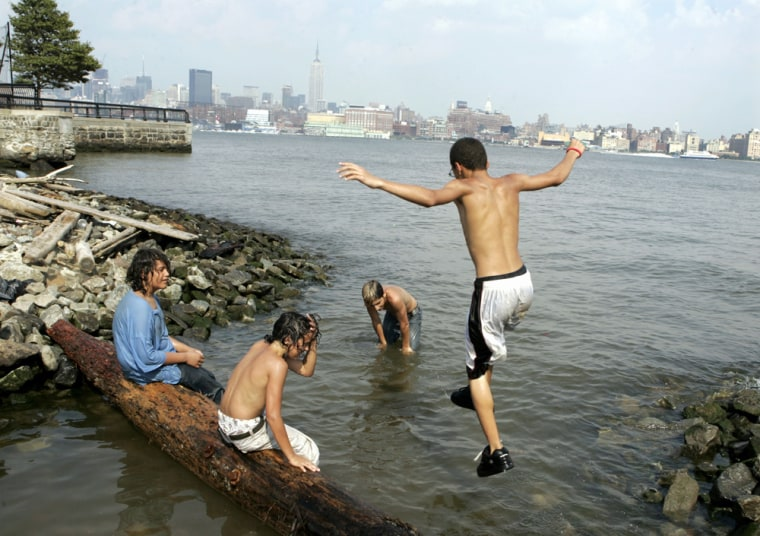 Julio Ferreira, right, jumps into the Hudson River as he cools off with friends in Hoboken, N.J., on Tuesday.