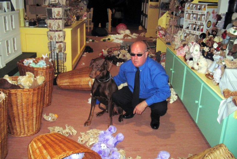 Security guard Greg West and his Doberman, Barney. A $75,000 teddy bear formerly owned by Elvis Presley was one of the bears destroyed when the guard dog went on the rampage on Tuesday.