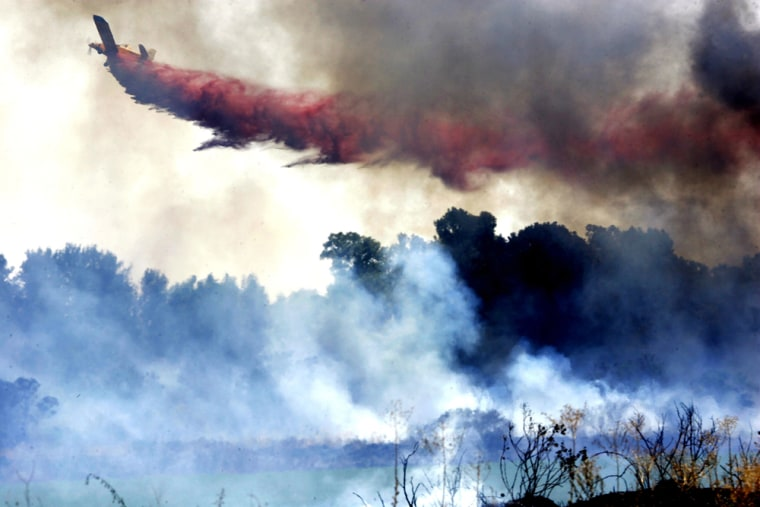 A plane releases powder to extinguish a fire caused by a rocket fired from south Lebanon toward the northern Israeli town of Kiryat Shmona on Monday.