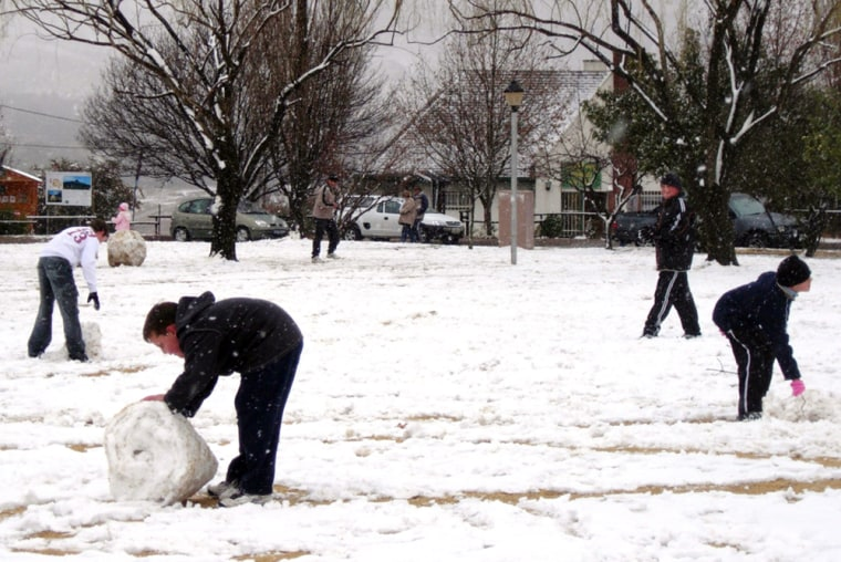 Residents frolic in the snow Wednesday in Clarens, South Africa. Heavy snow, rain and rockfalls closed mountain roads in parts of the interior, according to local news reports.