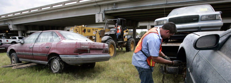 Worker prepares to tow abandoned car near highway overpass in New Orleans