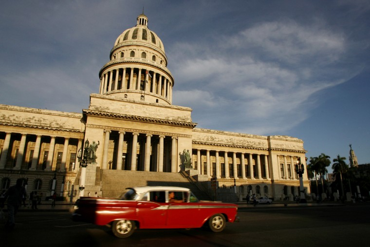 A vintagecar moves past the Capitol building in Havanaon Wednesday. By picking six comrades to run key projects while his brother acts as president and head of the Communist Party, Fidel Castro has set the stage for a more collective style of governance.