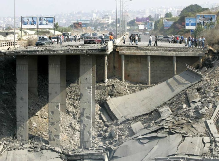 Lebanese civilians inspectdamage toHalat bridge, north of Beirut,after it was hitby Israeli warplanes onFriday.