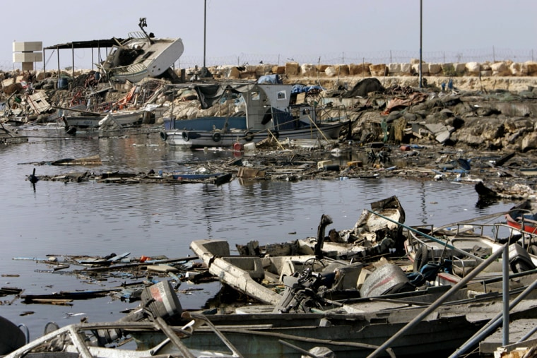 Fishing boats lie wrecked Friday atthe port of the southern Beirut suburb of Ouzai, Lebanon,after an Israeli airstrike. About 300 boats were destroyed. Why Israeli forces targeted the boats is unknown.