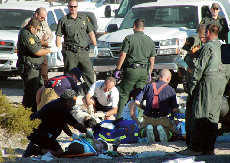 Rescuers and paramedics work at the scene of the accident involving a sport utility vehicle crowded with suspected illegal immigrants near Yuma, Ariz., Monday.