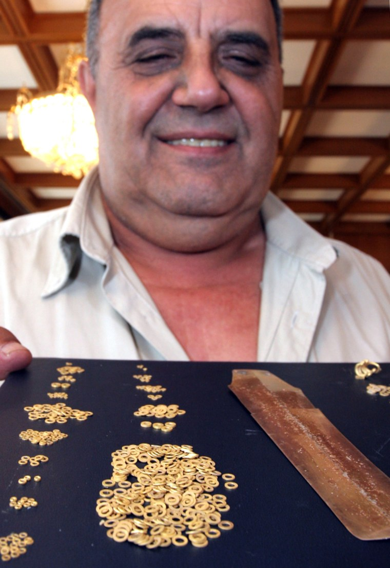 Bozhidar Dimitrov, the head of the Bulgarian National Museum of History, shows off a gold and platinum dagger, right, and pieces of jewelry believed to be 5,000 years old during abriefing in Sofia onMonday.