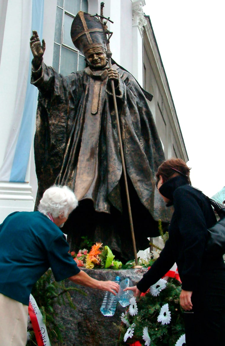 Pilgrims collect water at a statue of John Paul IIin Wadowice, Poland, on Saturday.