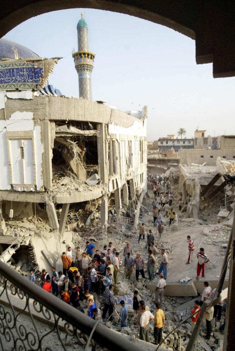 Iraqis inspect the destruction at the Sh