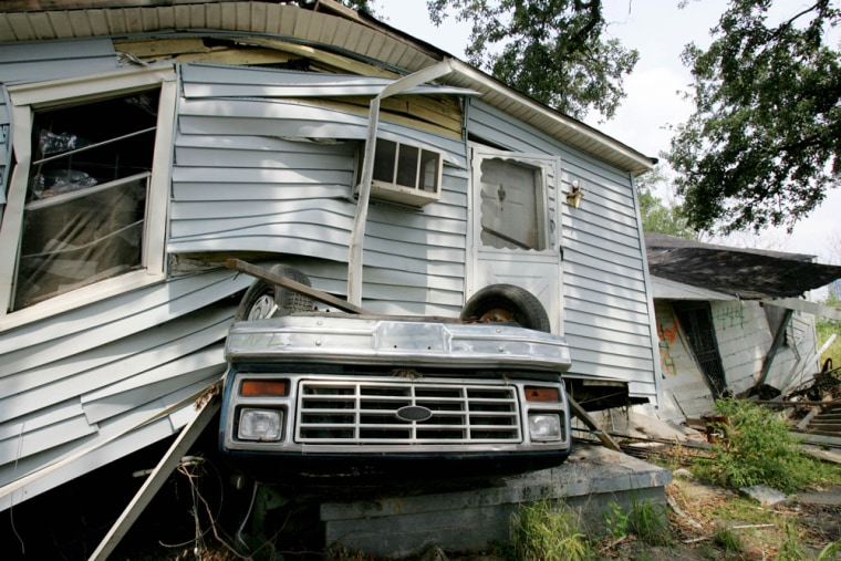 A truck still sits under a house in the Lower 9th Ward almost a year after Hurricane Katrina is New Orleans