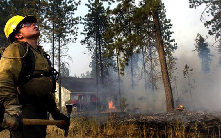 Department of Natural Resources firefighter Tyler Williams listens for a tanker overhead while monitoring a burn out  near Valley, Wash., on Tuesday.