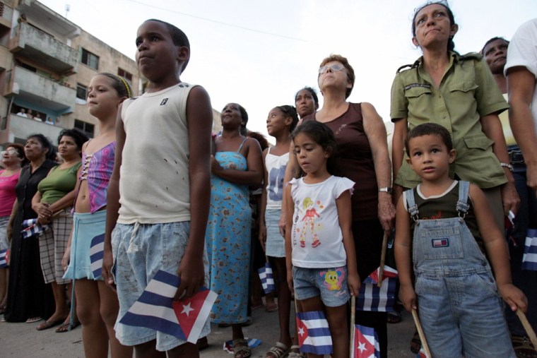 People listen to national anthem during rally in support of Cuba's President Castro in Havana