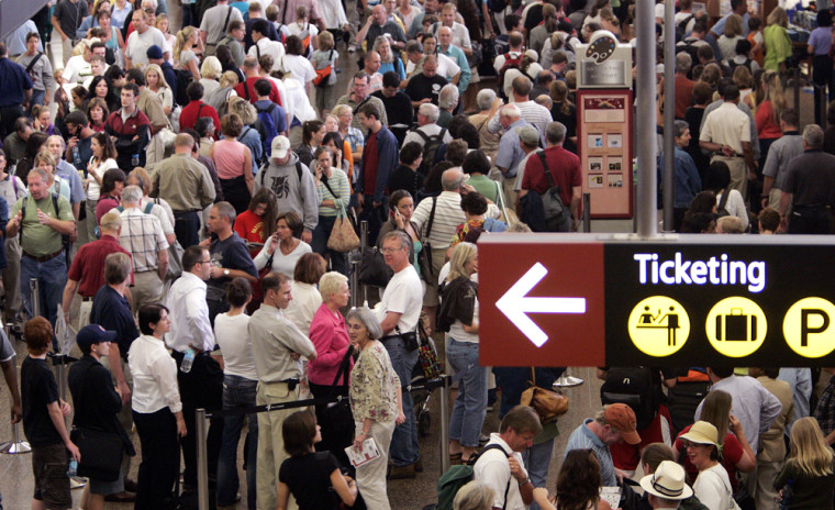 Travelers fill the concourse as they wait to go through a security checkpoint at the Sea-Tac International Airport in Seattle on Aug. 10.