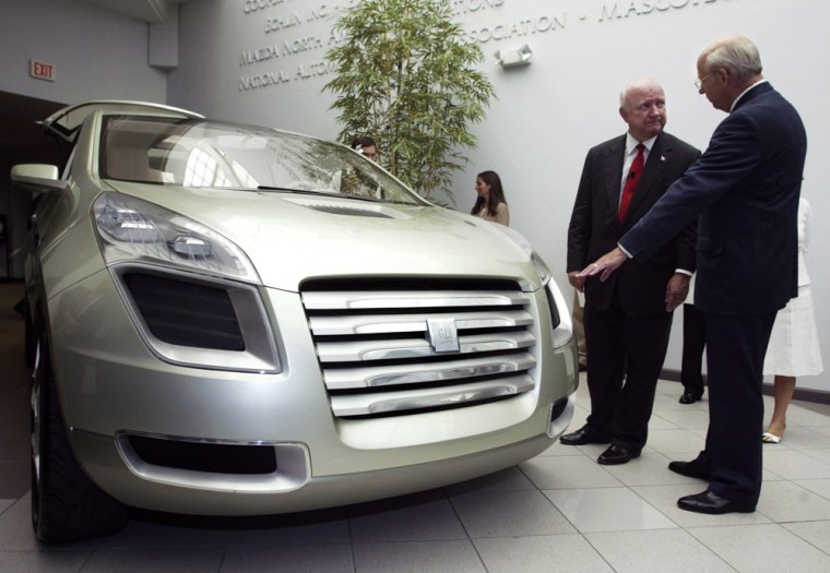 U.S. Secretary of Energy Samuel W. Bodman (left) gets a closer look at the General Motors Sequel fuel cell concept vehicle with GM Executive Vice President Tom Gottschalk, July 14, 2005 at the Automotive Hall of Fame in Dearborn, Michigan.