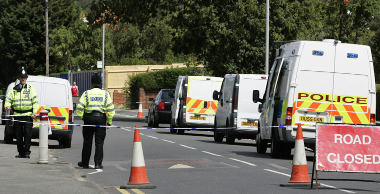 British police officers stand guard ona cordoned-off road in High Wycombe, England, on Friday after a massive security operation resulted inarrests across the United Kingdom.