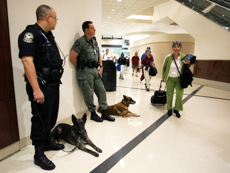 Atlanta Police K-9 Officers stand with their dogs as passengers pass by to go through security at Hartsfield-Jackson International Airport in Atlanta