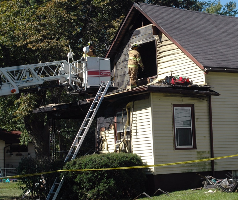 Firefighters continue the investigationat the scene of a house fire Sunday in Michigan City, Ind.