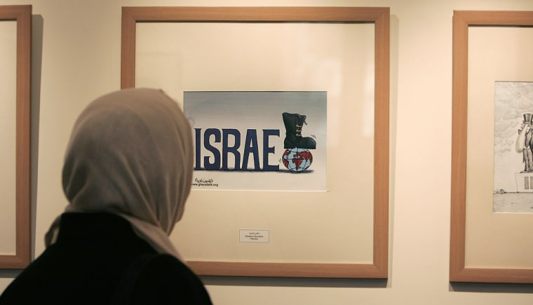An Iranian woman looks at an exhibit during a visit at the Holocaust International Cartoon Exhibition in Tehran