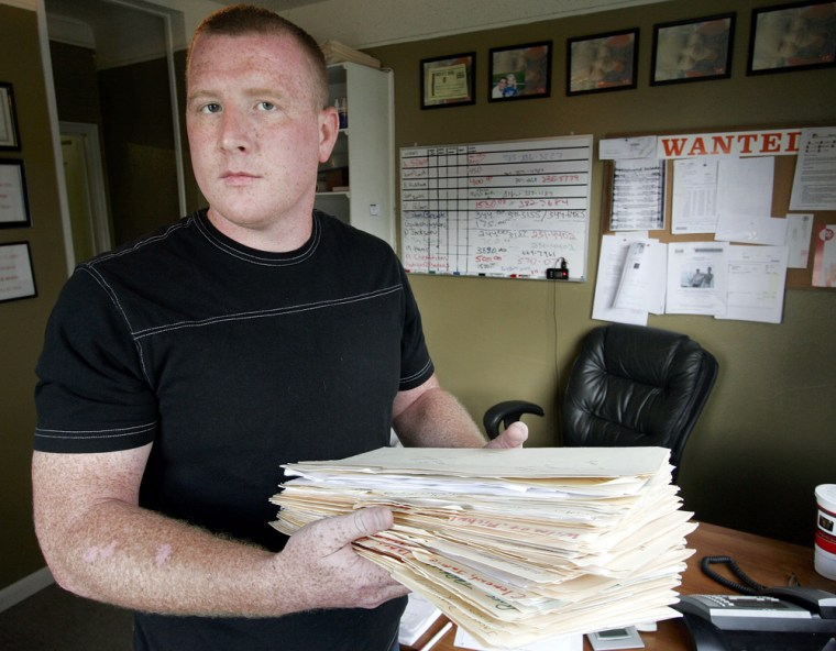 Michael Wright, a bounty hunter, holds case files of recent apprehensions in his office in Metairie, La., on Aug. 10. Houston took in 150,000 evacuees, most of any U.S. city, after Katrina struck. Now Houston police say evacuees are partly responsible for a nearly 17.5 percent increase in homicides so far over the same period in 2005.