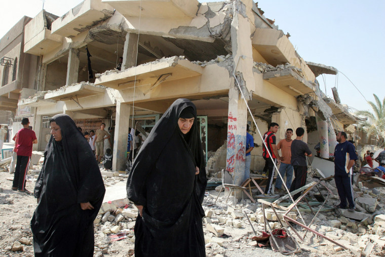 Two women walk past a destroyed residential building Monday in Baghdad.