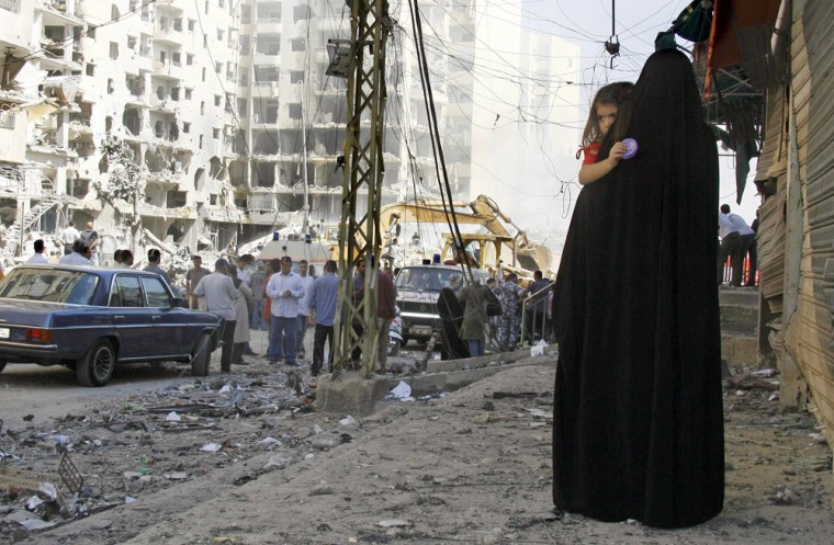 Lebanese Shiite Muslim looks at damage as she returns to home in Beirut's southern suburbs