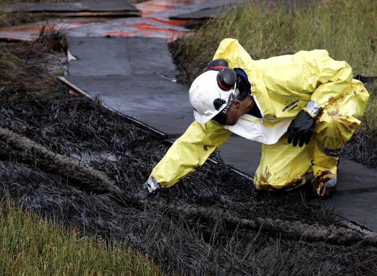 A worker uses a rope mop to clean up oil in tundra grass from a leak from an oil transit line at the Prudhoe Bay oil field on Alaska's North Slope last week.